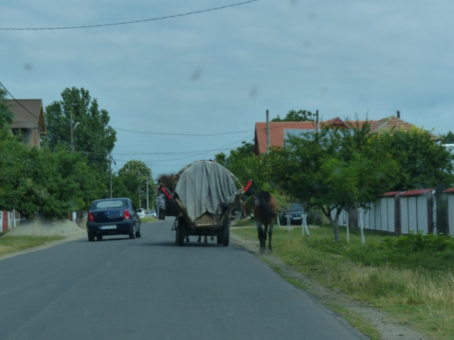A gypsy wagon being passed on the left.  No sidewalks.  No shoulder.  Lots of pedestrians and kids playing along the road.