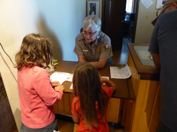 Park ranger reviewing booklets so children could receive their Junior Ranger badges.